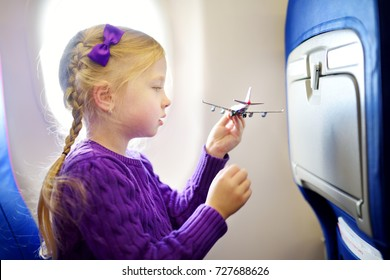 Adorable little girl traveling by an airplane. Child sitting by aircraft window and playing with toy plane. Traveling abroad with kids.