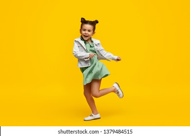Adorable little girl in trendy dress and jacket cheerfully smiling and twisting on one leg while dancing against bright yellow background