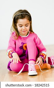 adorable little girl tying her shoes