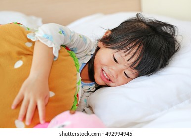 Adorable little girl wake up on the morning, Little cute girl lying on the bed