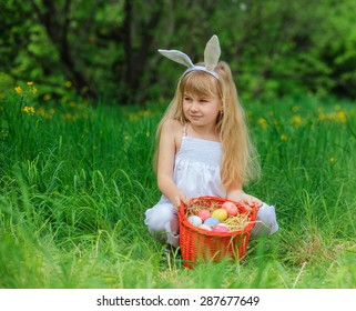 Adorable little girl wearing bunny ears playing with Easter eggs in blossoming dandelion on spring day