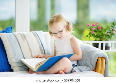 Adorable little girl wearing eyeglasses reading a book in white living room on beautiful summer day