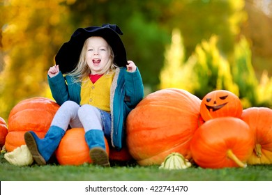 Adorable little girl wearing halloween costume having fun on a pumpkin patch on beautiful autumn day