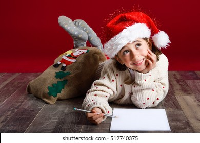 Adorable little girl wearing santa hat writing Santa letter on wooden floor. Winter clothes for Christmas.