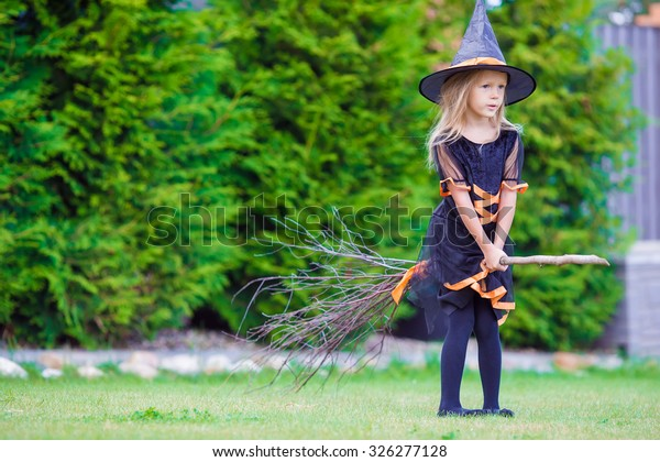 Adorable little girl wearing witch costume on Halloween at autumn day. Trick or treat.