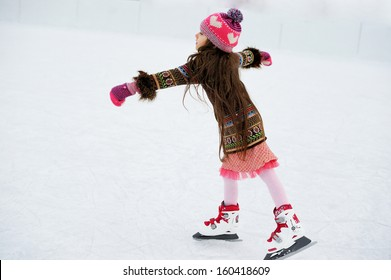 Adorable little girl in winter clothes and bobble hat skating on ice rink