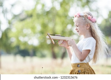 Adorable little girl with wood crossbow. Funny shooting. Flowing hair