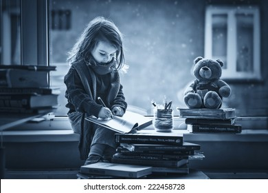 Adorable little girl, writing letter to Santa, sitting on a window, books and teddy bear around