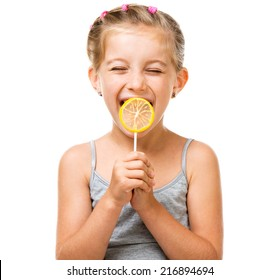 Adorable little girl with yellow lemon lollipop isolated over white background