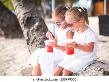 Adorable little girls drinking fresh watermelon on tropical beach
