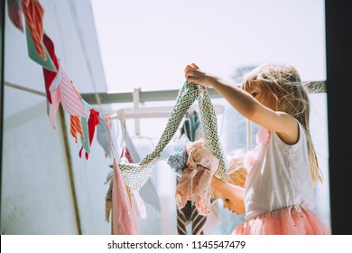 Adorable little girls hanging out the laundry on sunny day on the balcony
