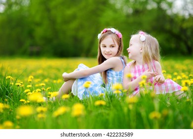 Adorable little girls having fun together in blooming dandelion meadow on beautiful spring day