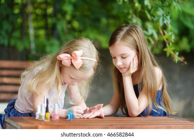 Adorable little girls having fun playing at home with colorful nail polish doing manicure and painting nails to each other
