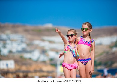 Adorable little girls having fun during beach vacation on Mykonos