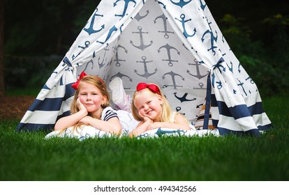Adorable little girls having fun playing outdoors on summer day with sea style teepee