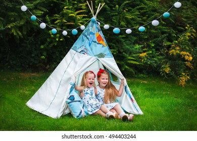Adorable little girls having fun playing outdoors on summer day with teepee
