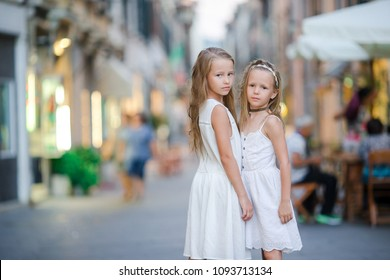 Adorable little girls in Pietrasanta in Toscany. Portrait of kids walking at small italian town on italian vacation