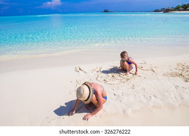 Adorable little girls playing with beach toys during tropical vacation