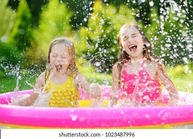 Adorable little girls playing in inflatable baby pool. Happy kids splashing in colorful garden play center on hot summer day. Summer activities for kids.
