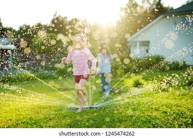 Adorable little girls playing with a sprinkler in a backyard on sunny summer day. Cute children having fun with water outdoors. Funny summer games for kids.