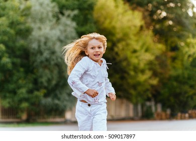 Adorable little girls running with big smile on face. Summer vacation concept.