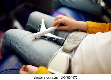 Adorable little girls traveling by an airplane. Children sitting by aircraft window and playing with toy plane. Traveling abroad with kids.