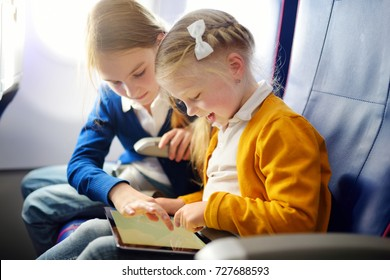 Adorable little girls traveling by an airplane. Children sitting by aircraft window and using a digital tablet during the flight. Traveling abroad with kids.