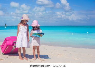 Adorable little girls walking big suitcase and map searching the way on tropical beach