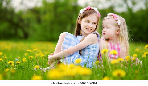 Adorable little girls wearing wreaths in blooming dandelion meadow on beautiful spring day. Children having fun outdoors picking fresh flowers.