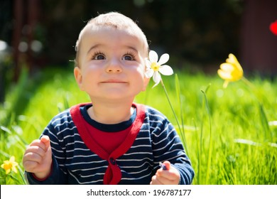 Adorable little happy smiling baby boy playing in a blooming garden between the flowers