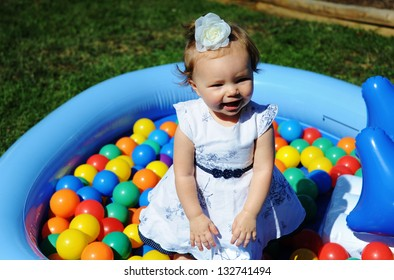 Adorable little infant girl playing in a colorful ball pit at a summer picnic.