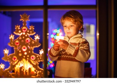 Adorable little kid boy, blond child standing by window at Christmas time and holding candle. With colorful lights from Christmas tree on background. Holiday, lifestyle, xmas concept