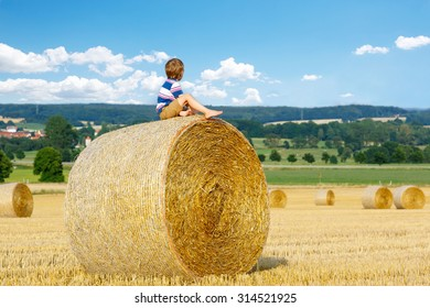 Adorable little kid boy in traditional German bavarian clothes, leather shorts and check shirt. Child sitting on hay stack or bale and dreaming. Active outdoors leisure on warm summer day.