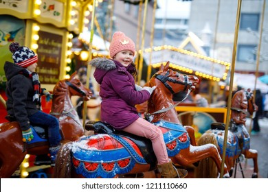 Adorable little kid girl riding on a merry go round carousel horse at Christmas funfair or market, outdoors. Happy child having fun on traditional family xmas market in Munich, Germany