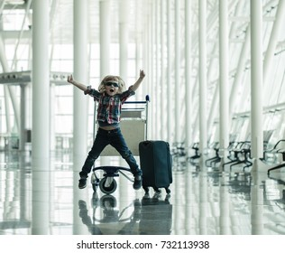 Adorable little kid jumping in airport. Happy travel concept. Child with baggage enjoys holiday. Vacation in Portugal.
