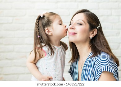 Adorable little kid kissing her mother in living room at home