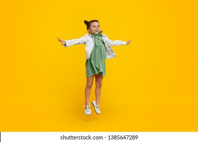Adorable little kid in stylish dress smiling and stretching out arms while leaping up against yellow background