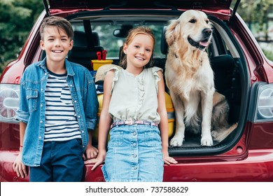 adorable little kids with dog in car trunk