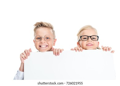 adorable little kids in eyeglasses holding blank banner and smiling at camera isolated on white