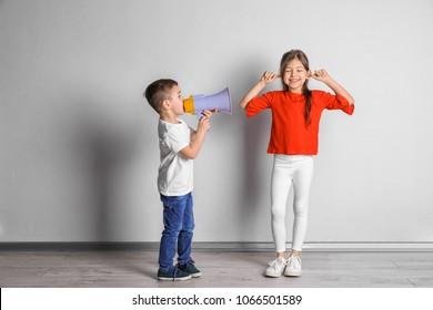 Adorable little kids with megaphone near light wall