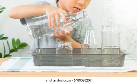 Adorable little kindergarten child, boy pours water from glass jar into bottle with care, focus and concentration. Montessori, Child Development Activity, Practical Life Skills, Hand Eye Coordination.