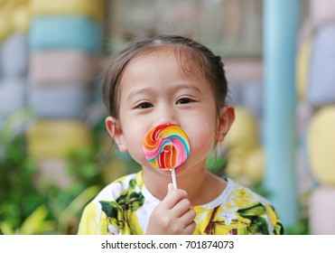 Adorable little laughing girl holding big colorful lollipop
