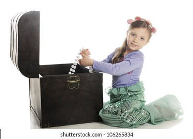An adorable little mermaid pulling strands of large pearls from an old treasure chest.  On a white background.
