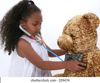 Adorable Little Playing Doctor To A Teddy Bear Over White.