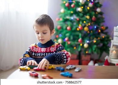 Adorable little preschool boy, playing with toy cars at home on Christmas, Christmas decoration around him