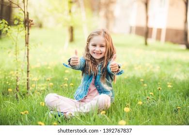 Adorable little preteen girl enjoying nice summer sunny days in park