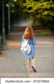 Adorable little red-haired girl going to school, rear view