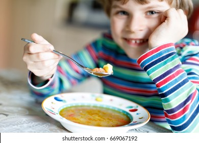 Adorable little school boy eating vegetable soup indoor. Blond child in domestic kitchen or in school canteen. Selective focus on hand of kid.