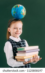 adorable little schoolchild with globe on head holding pile of books and smiling at camera