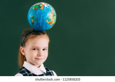 adorable little schoolchild with globe on head smiling at camera while standing near blackboard